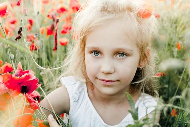 Porträt eines mädchens unter dem mohnblumenfeld