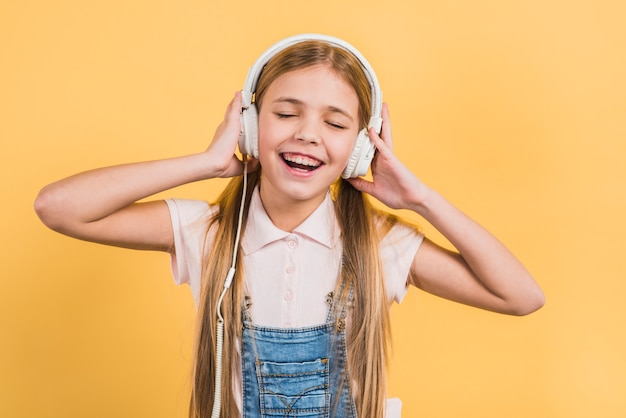 Porträt eines mädchens, welches die musik auf dem kopfhörer steht gegen gelben hintergrund genießt