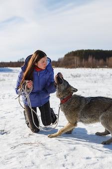 Porträt eines mädchentrainers und des grauen wolfs auf einem schneebedeckten gebiet
