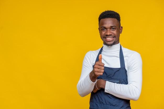 Porträt eines männlichen afrikanischen kochs, der lächelt und eine geste mit dem daumen nach oben macht
