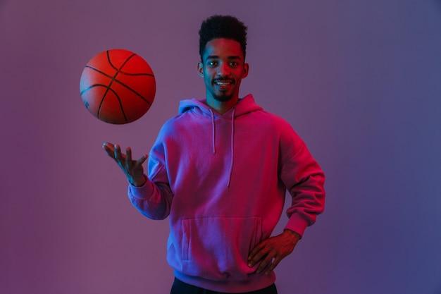 Porträt eines männlichen afroamerikanischen mannes in einem bunten hoodie, der mit basketball isoliert über einer violetten wand posiert