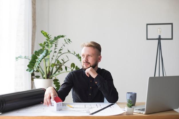 Porträt eines männlichen architekten mit hausmodell auf architektenplan am arbeitsplatz