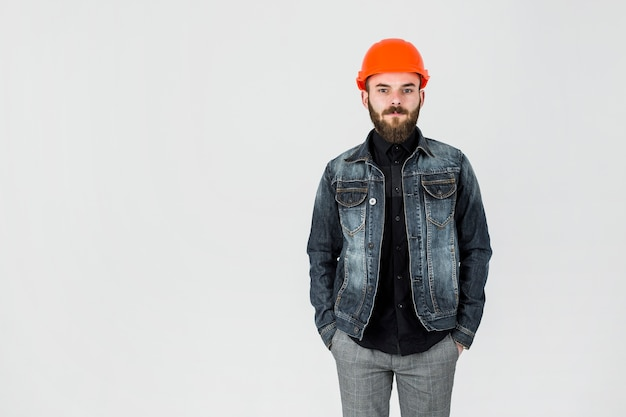 Porträt eines männlichen architekten tragenden hardhat, der gegen weißen hintergrund steht