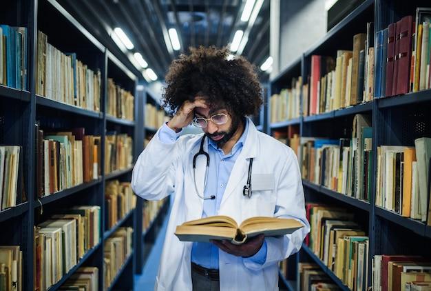 Porträt eines männlichen arztes, der in der bibliothek steht und informationen über das koronavirus studiert.