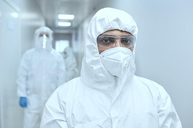 Porträt eines männlichen arztes in schutzuniform und maske, der die kamera anschaut, während er im flur steht und während der pandemie arbeitet