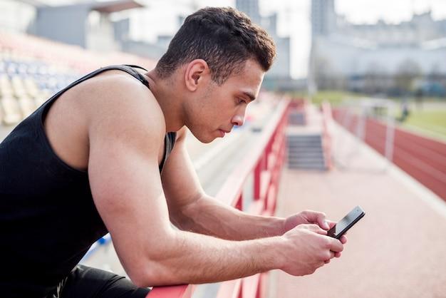 Porträt eines männlichen athleten, der handy am stadion verwendet