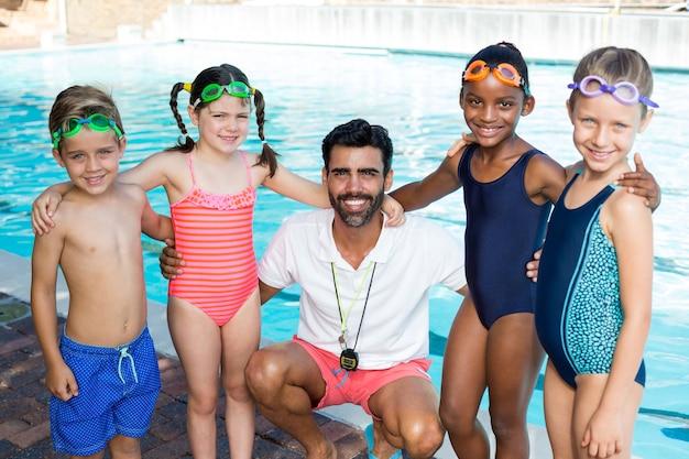 Porträt eines männlichen ausbilders mit kleinen schwimmern am pool