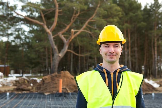Porträt eines männlichen baumeisters in einem gelben helm und einer schutzweste