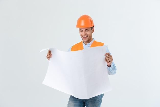 Porträt eines männlichen bauunternehmer-ingenieurs mit schutzhelm, der blaupausenpapier hält. getrennt über weißem hintergrund.