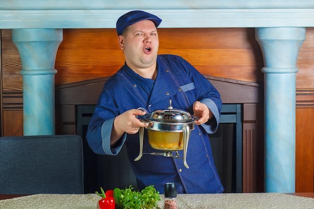Porträt eines männlichen chefkochs, der wanne hält.