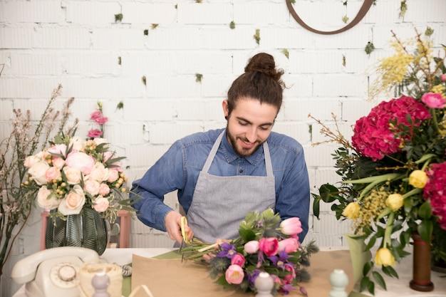 Porträt eines männlichen floristen, der den blumenblumenstrauß im blumenladen einwickelt