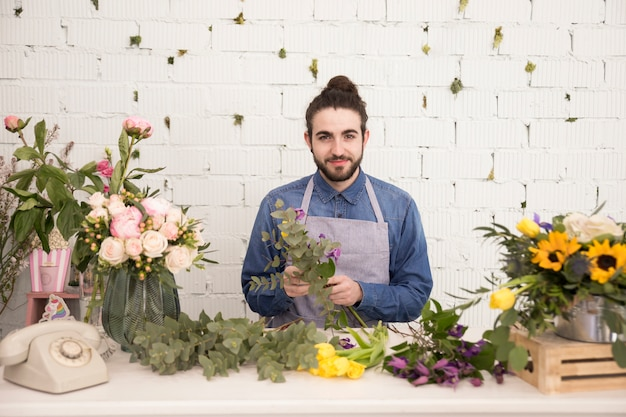Porträt eines männlichen floristen, der den blumenblumenstrauß steht gegen weiße wand macht