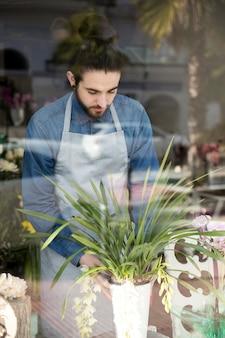 Porträt eines männlichen floristen, der den vase gesehen durch glas platziert