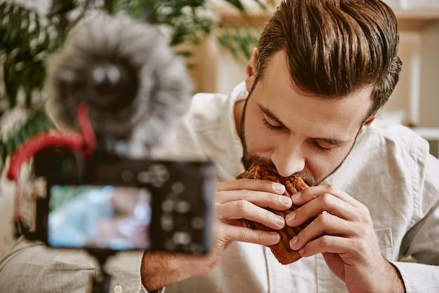 Porträt eines männlichen food-bloggers, der ein sandwich isst, während er ein neues video für seinen youtube-kanal erstellt