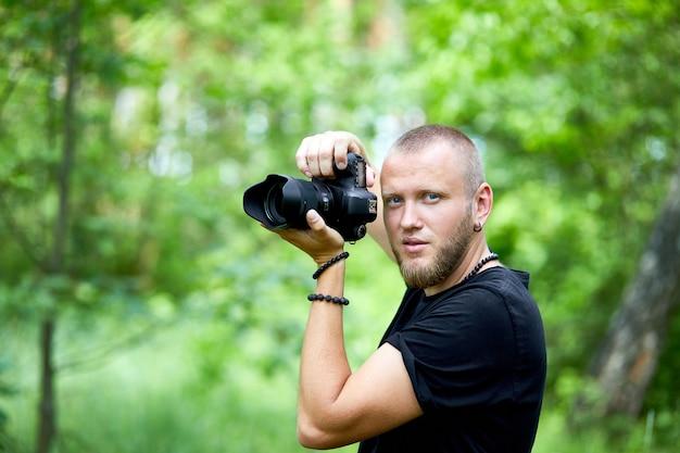 Porträt eines männlichen fotografen, der ihr gesicht mit der kamera bedeckt