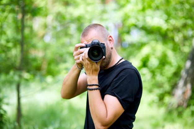Porträt eines männlichen fotografen, der ihr gesicht mit der kamera im freien bedeckt, fotografieren, weltfotografentag, junger mann mit einer kamera in der hand.