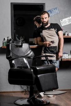 Porträt eines männlichen friseurs mit dem bart, der im friseursalon steht