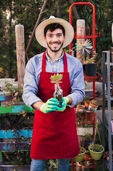 Porträt eines männlichen gärtners, der in der hand kaktuspflanze hält