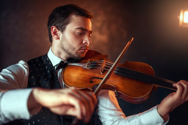 Porträt eines männlichen geigers, der klassische musik auf geige spielt. geiger mit musikinstrument