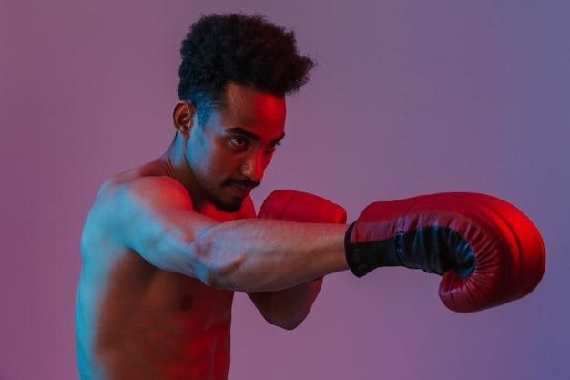 Porträt eines männlichen halbnackten afroamerikaners, der in boxhandschuhen posiert, die über einer violetten wand isoliert sind