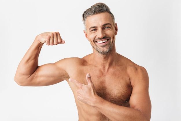 Porträt eines männlichen halbnackten mannes 30er jahre mit borstenlächeln und zeigt seinen bizeps isoliert auf weiß