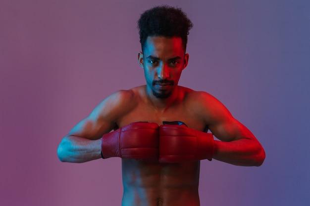 Porträt eines männlichen hemdlosen afroamerikanischen sportlers, der in boxhandschuhen posiert, die über einer violetten wand isoliert sind?
