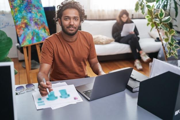 Porträt eines männlichen indischen designers und stylisten, der seine arbeit am tisch im hintergrund seiner kollegin macht, die sie auf dem sofa sitzt.