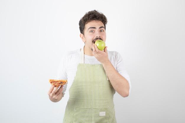Porträt eines männlichen kochs, der apfel statt pizza auf weiß isst