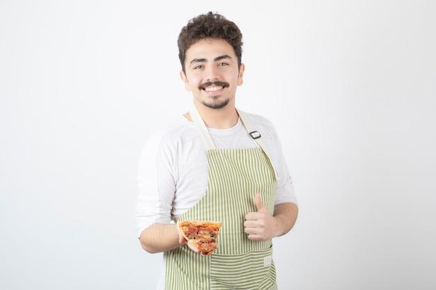 Porträt eines männlichen kochs, der ein stück pizza hält und daumen hochgibt