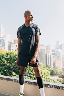 Porträt eines männlichen läufers des athleten, der auf dachspitze steht