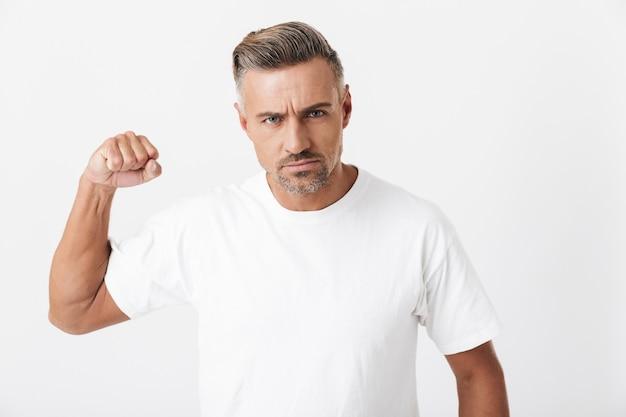 Porträt eines männlichen mannes der 30er jahre mit borsten, der ein lässiges t-shirt trägt, das seinen bizeps isoliert auf weiß zeigt