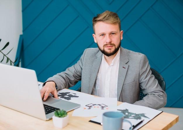 Porträt eines männlichen psychologen, der in seinem büro mit rorschach inkblot-testpapier unter verwendung des laptops sitzt