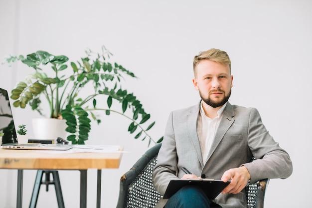 Porträt eines männlichen psychologen, der in seiner büroschreibensanmerkung über klemmbrett sitzt