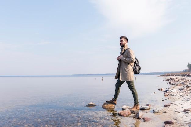Porträt eines männlichen reisenden, der nahe dem see mit seinem rucksack steht