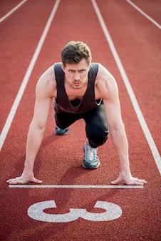 Porträt eines männlichen sprinters bereit zum rennen auf rennbahn