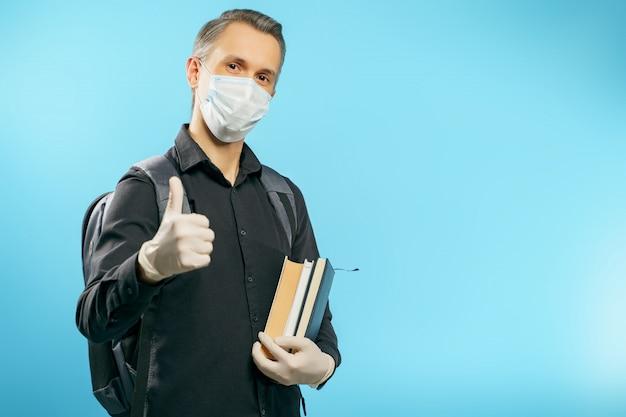 Porträt eines männlichen studenten in einer medizinischen schutzmaske und in den handschuhen, die bücher halten und einen daumen auf blau zeigen.