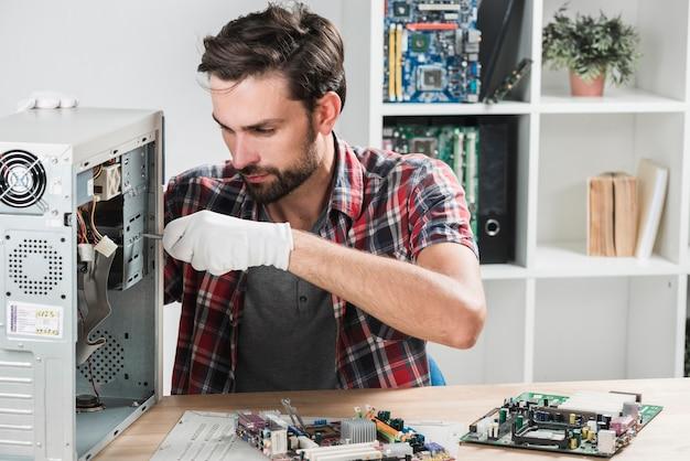 Porträt eines männlichen technikers, der computer repariert
