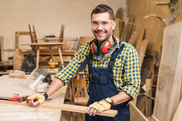 Porträt eines männlichen tischlers, der hölzerne planke auf werktisch in der werkstatt hält