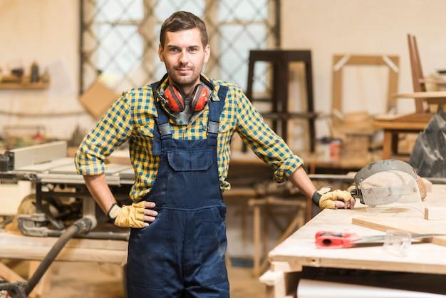 Porträt eines männlichen tischlers mit seiner hand auf der hüfte, die nahe dem werktisch steht