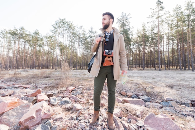 Porträt eines männlichen wanderers, der eine generische karte im wald weg schaut hält