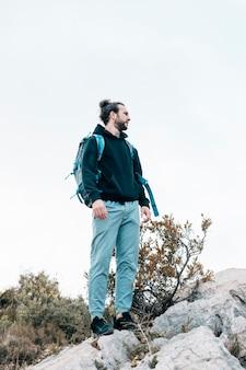 Porträt eines männlichen wanderers mit seinem rucksack, der auf felsigem berg steht