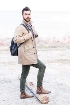 Porträt eines männlichen wanderers mit seinem rucksack, der mit seinem fuß auf klotz steht