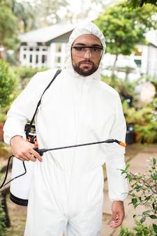 Porträt eines männlichen wissenschaftlers, der pestizide sprüht