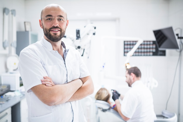 Porträt eines männlichen zahnarztes mit den gefalteten händen
