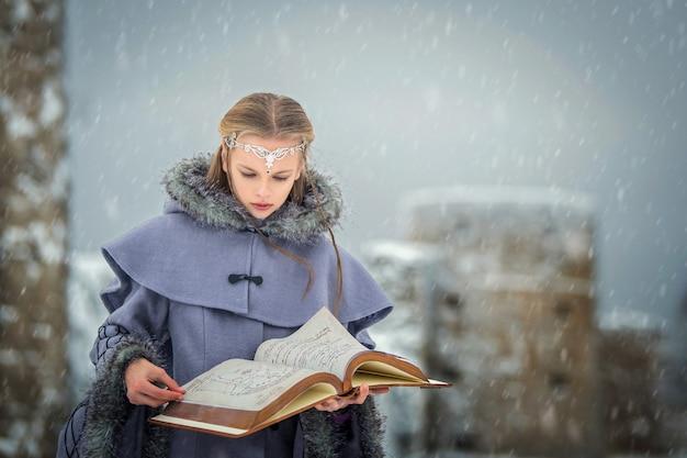 Porträt eines märchenhaften elfenmädchens mit einem magischen buch in ihren händen vor dem hintergrund der winternatur und der magischen festung