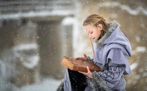 Porträt eines märchenhaften elfenmädchens mit einem magischen buch in ihren händen vor dem hintergrund des winters