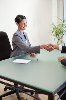 Porträt eines managers, der die hand eines kunden rüttelt