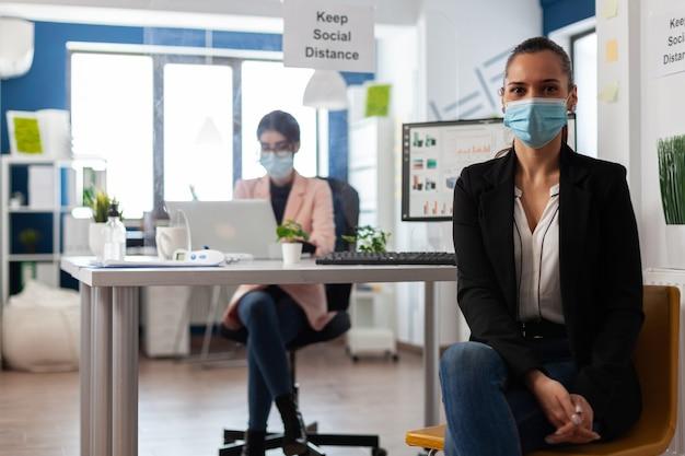 Porträt eines managers, der eine medizinische gesichtsmaske gegen coronavirus trägt