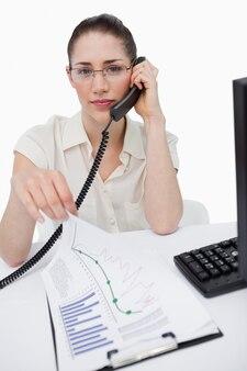 Porträt eines managers, der einen anruf beim betrachten von statistiken macht