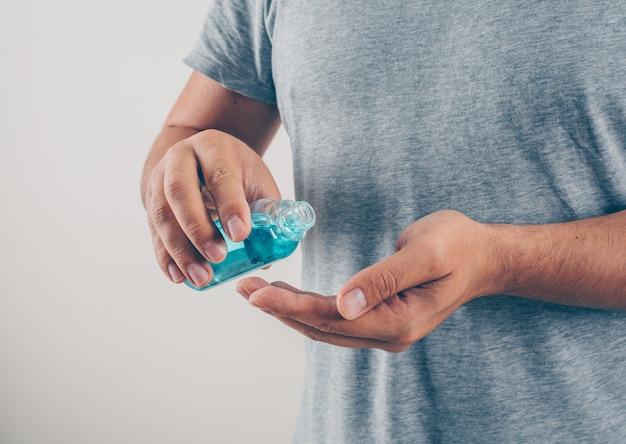 Porträt eines mannes am weißen hintergrund, der seine hand im grauen t-shirt desinfiziert